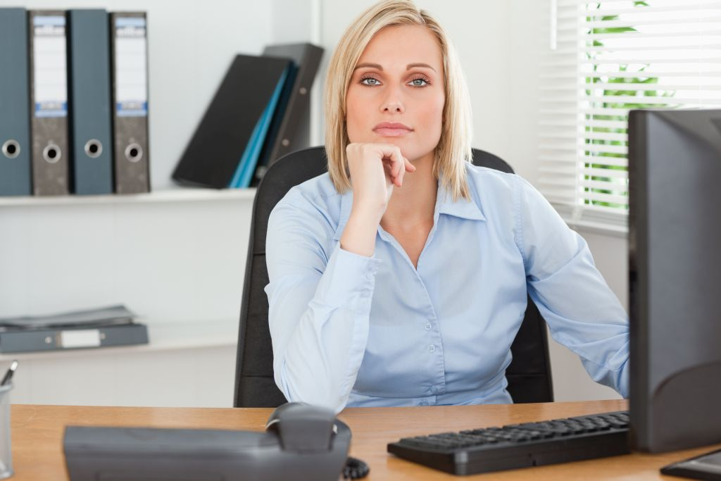 Serious woman with chin on hand behind a desk